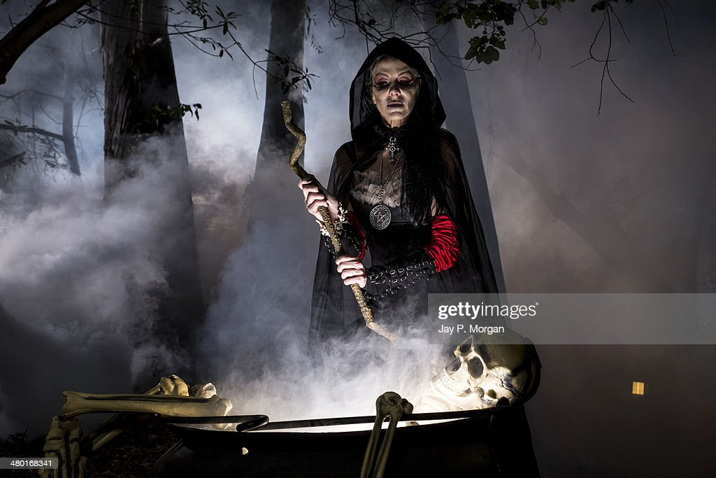 Witch stirring kettle in the forest