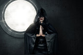Image of witch wearing black hood casting spell