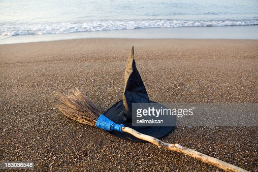 Witch's Hat And Broom On Beach Sand By Sea Vawes