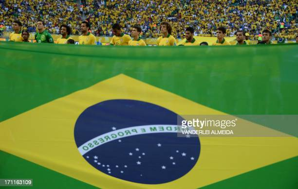 With a Brazilian national flag on the foreground Brazil's players listen to the national anthems before the start of their FIFA Confederations Cup...