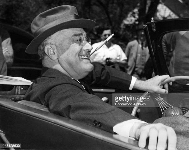 With a cigarette in a holder clenched in his teeth a smiling Franklin Delano Roosevelt sits jauntily at the wheel of his convertible Warm Springs...