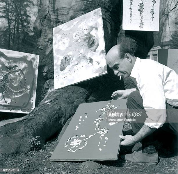 With a cigarette in his mouth Lucio Fontana places one of his canvas on the big roots of a tree in the garden of his study in Corso Monforte founder...