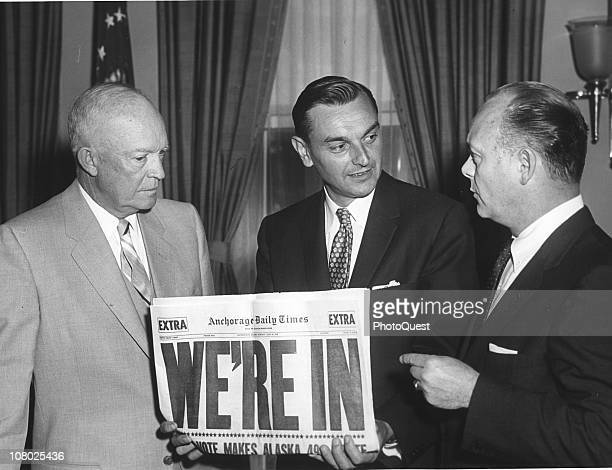 WIth a copy of Anchorage Daily News headlined 'We're In' US President Dwight Eisenhower poses with Governor of the Alaska Territories Mike Stepovich...