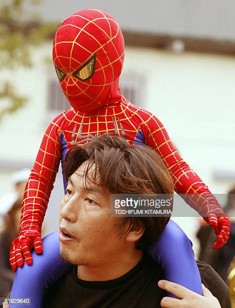 With a costume of the spiderman a boy is carried by his father to participate in the Halloween parade at the Omotesando district in Tokyo 31 October...