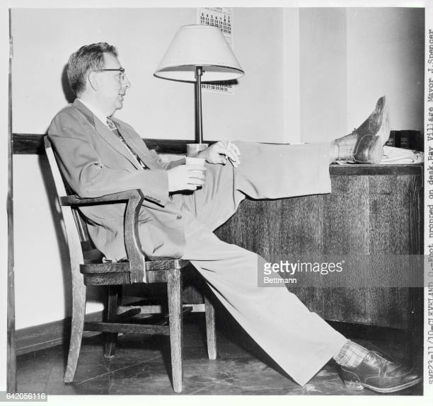 With a foot propped on his desk Bay Village Mayor J Spencer Houk relaxes with a cigarette and coffee after testifying Nov10th in the first degree...