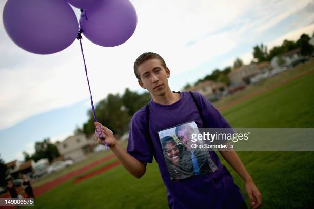 With a photograph of movie theater shooting victim AJ Boik and his girlfriend taped to his shirt Zephaniah Baca joins family friends and former...