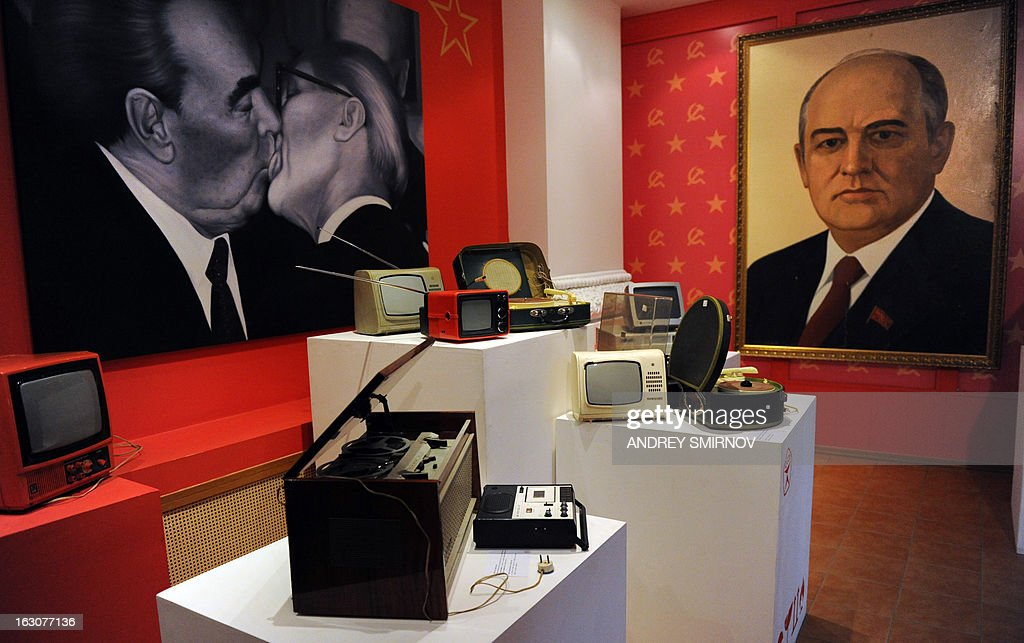 With a portrait of former Soviet Union President Mikhail Gorbachev (R) and a pictured featuring a kiss between then Soviet leader Leonid Brezhnev and Erich Honecker (L) hanging on walls Soviet-era portable transistor TV and radio sets are displayed at the Museum of the Soviet Union in Moscow on March 4, 2013. The museum displays an exhibition of objects reflecting all aspects of life in the Soviet State, the museum officials said. AFP PHOTO / ANDREY SMIRNOV