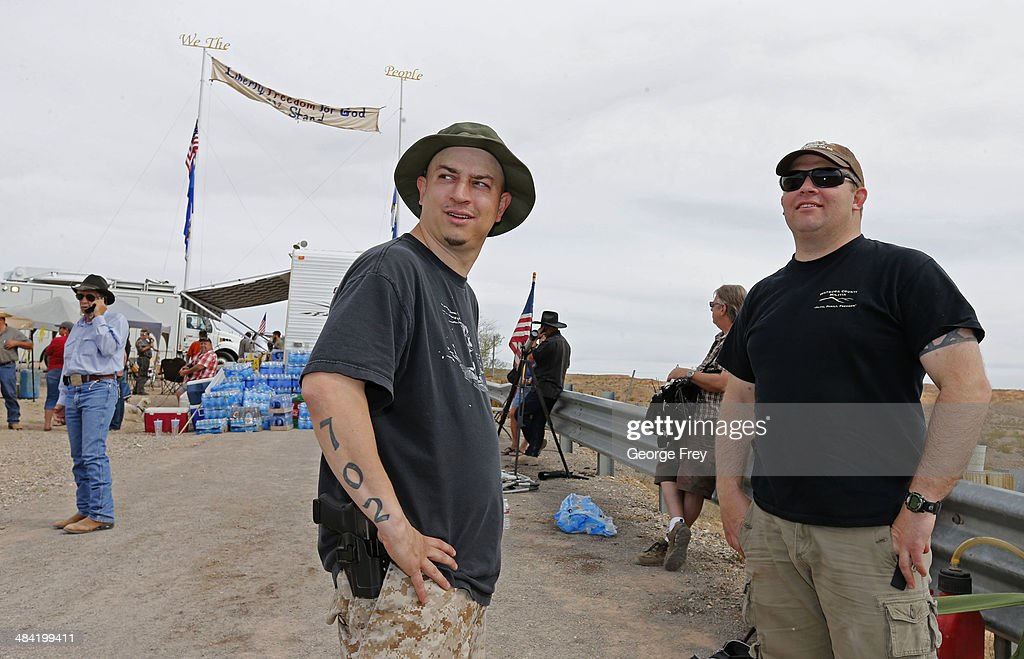 With a sidearm strapped to his side, Anthony Herrea (L) and another unidentified person, (R) stands along a protest area along U.S. 170 April 11, 2014 west of Mesquite, Nevada. Bureau of Land Management officials are rounding up Cliven Bundy's cattle, he has been locked in a dispute with the BLM for a couple of decades over grazing rights. (Photo by George Frey/Getty Images