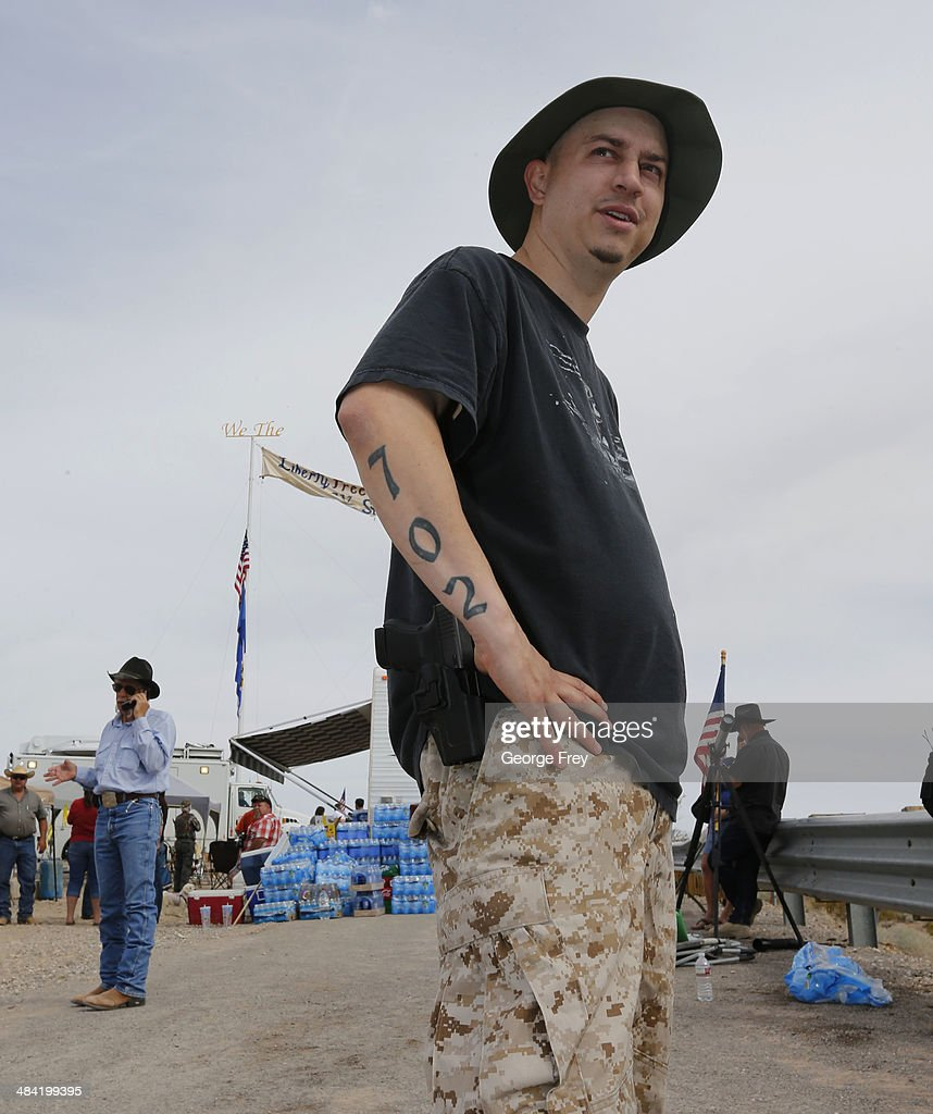 With a sidearm strapped to his side, Anthony Herrea stands along a protest area along U.S. 170 April 11, 2014 west of Mesquite, Nevada. Bureau of Land Management officials are rounding up Cliven Bundy's cattle, he has been locked in a dispute with the BLM for a couple of decades over grazing rights. (Photo by George Frey/Getty Images