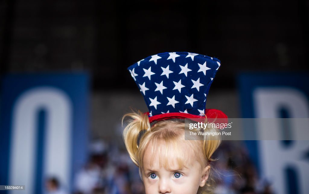 With a sign behind spelling out JOB, Delaney McGannon-Bilder, 18-months-old, from Bloomfield, waits with her mother, not shown, for Republican nominee for President Governor Mitt Romney to speak during a rally at Wings Over The Rockies Aviation and Space Museum in Denver, Colorado, on Monday evening, October, 1, 2012.