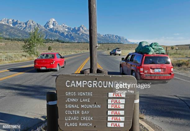 With a sign showing full camp grounds cars drive into Grand Teton National Park on August 19 2017 outside Jackson Wyoming People are flocking to the...