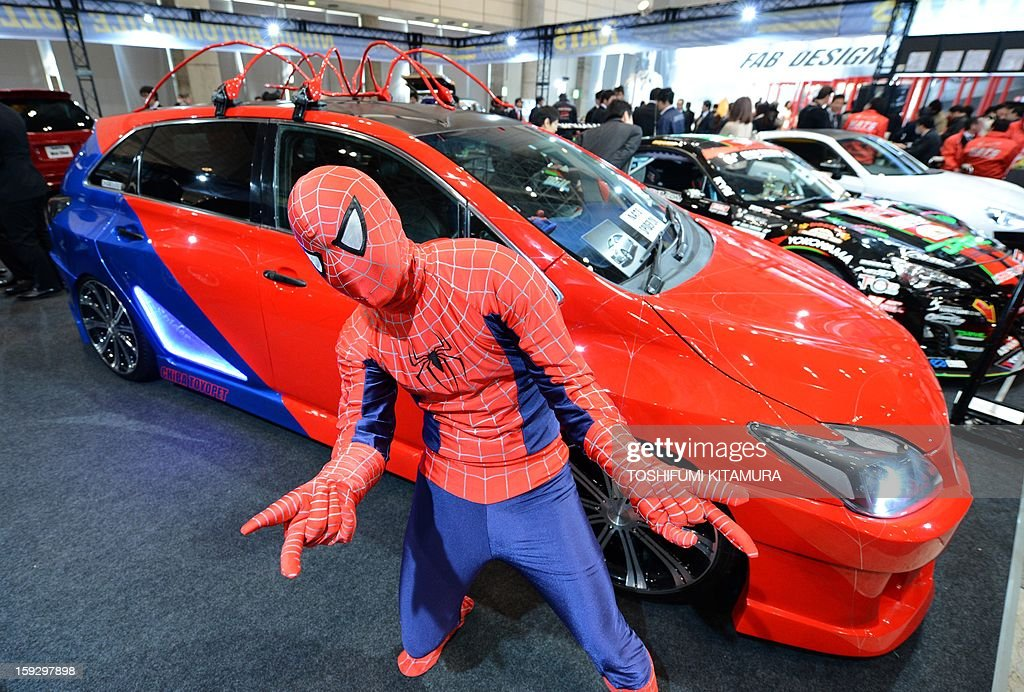 With a Spiderman-costume, a student poses in front of a Toyota Mark-X based vehicle, designed by NATS (Japan Automobile Collage) students, displayed during the Tokyo Auto Salon 2013 exhibition at the Makuhari Messe in Chiba on January 11, 2013. A total of 452 domestic and foreign companies participated in the three-day-long custom car exhibition with some 800 vehicles on display.