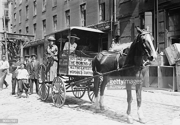 With a Suffragette at the reigns a Horse Drawn Women's Suffrage Cart On its way to Boston men look on as Photo is taken before the wagon again...