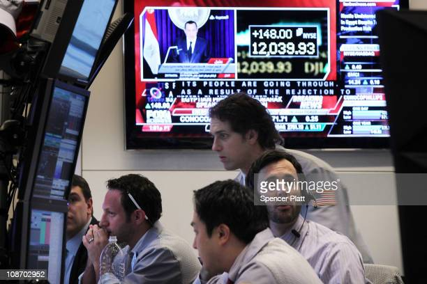 With a television screen showing Egyptian President Hosni Mubarak responding to the unrest in Egypt traders work on the floor of the New York Stock...