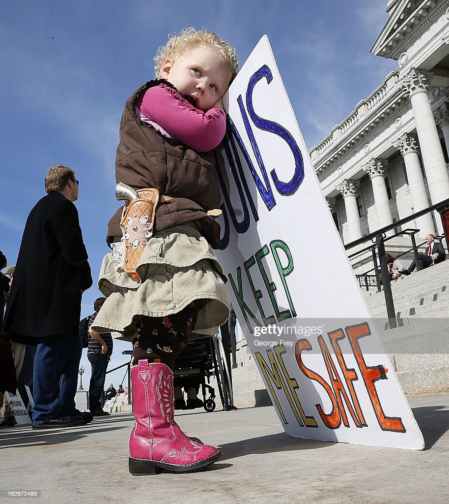 With a toy side arm two year old Arianna Ludlun holds a sign at a gun rights rally and march at the Utah State Capitol on March 2, 2013 in Salt Lake City, Utah. The rally attracted several hundred people for the march to the Utah Capitol in favor of 2nd Amendment rights as gun control supporters call for more limits and bans on assault weapons.