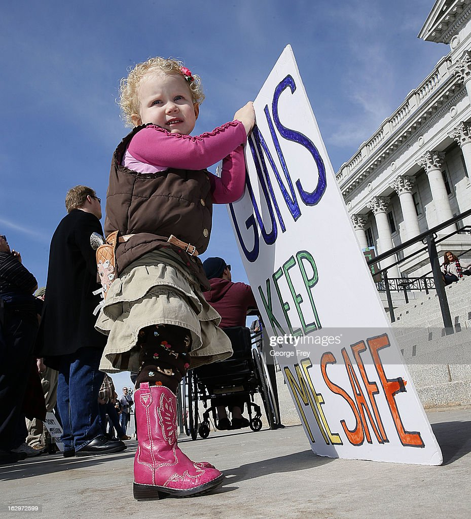 With a toy side arm two year old Arianna Ludlun holds a sign at a gun rights rally and march at the Utah State Capitol on March 2, 2013 in Salt Lake City, Utah. Gun Rights activists marched to the state Capital as gun control supporters call for more limits and bans on assault weapons.