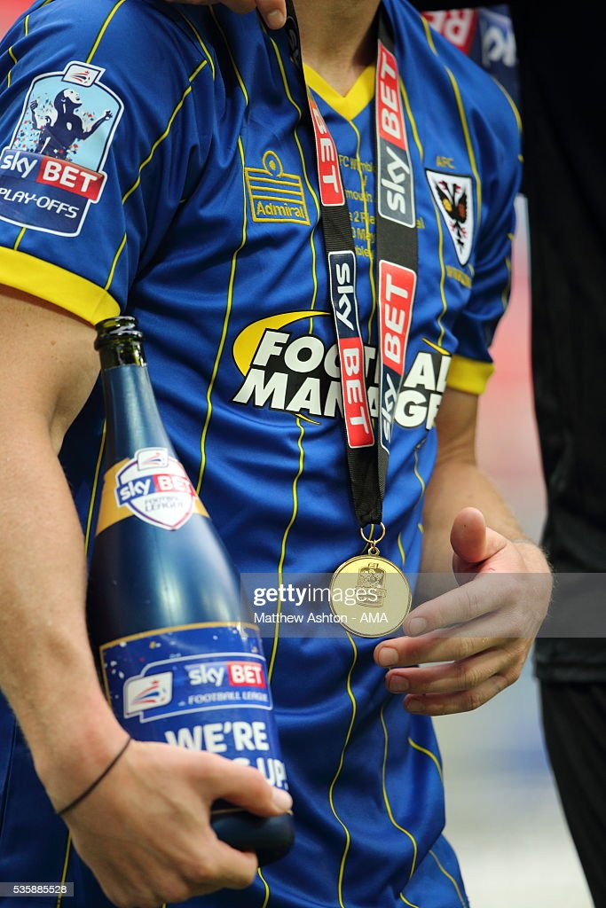 With a winners medal around his neck, Dannie Bulman of AFC Wimbledon celebrates promotion by holding the branded champagne bottle after victory in the Sky Bet League Two Play Off Final between Plymouth Argyle and AFC Wimbledon at Wembley Stadium on May 30, 2016 in London, England.