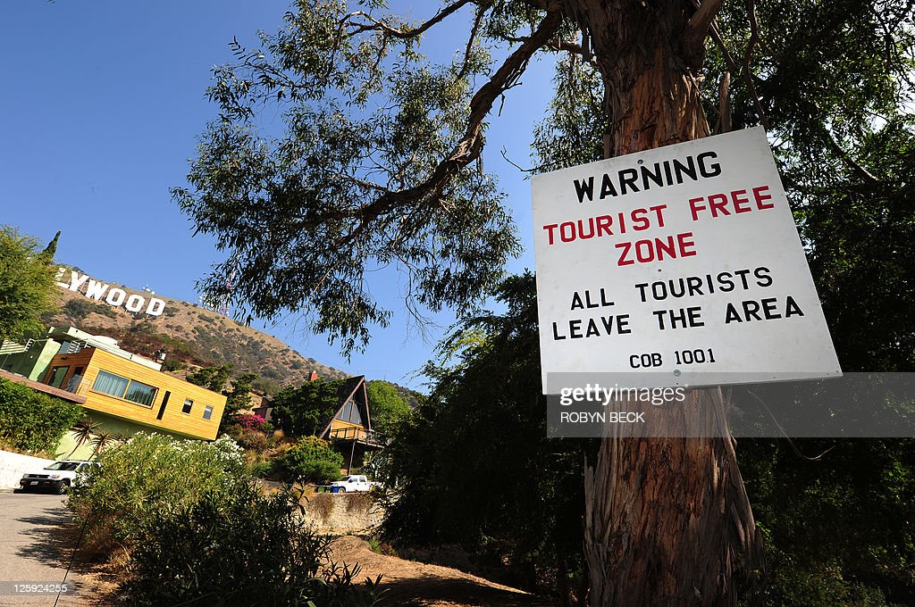 US-environment-technology-tourism A placard warning of a 'Tourist Free Zone' is posted along a road often used by tourists and locals to get a close up view of the iconic sign, in the residential Hollywood Hills section of Hollywood, California, September 21, 2011. Travelers have long flocked to have their pictures taken with the vast sign behind them -- but with the advent of satellite navigation and Google Earth, they have begun to invade the Hollywood Hills neighborhood like never before.