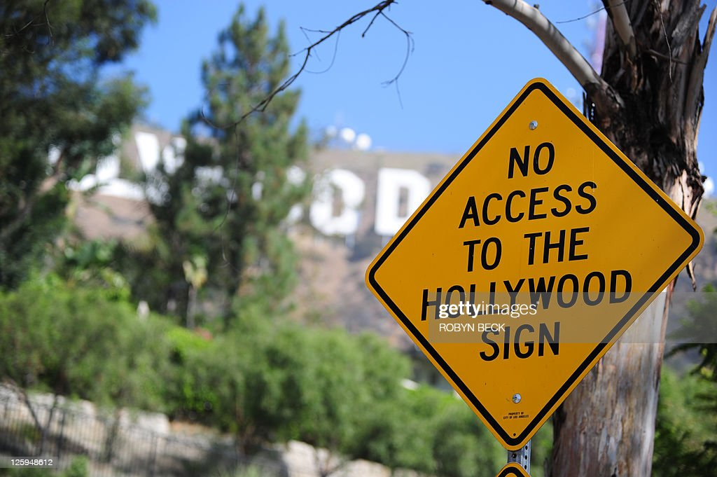US-environment-technology-tourism A placard advising sightseers that there is no access to the Hollywood sign is posted along a road often used by tourists and locals to get a close up view of the iconic sign, in the residential Hollywood Hills section of Hollywood, California, September 21, 2011. Travelers have long flocked to have their pictures taken with the vast sign behind them -- but with the advent of satellite navigation and Google Earth, they have begun to invade the Hollywood Hills neighborhood like never before.