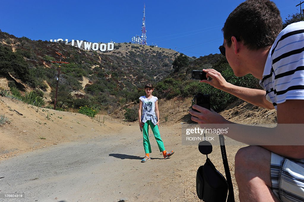 US-environment-technology-tourism Polish tourist Pawel Stepien, 18, takes a photo of his sister Katie Stepien, 11, in front of the Hollywood sign in a residential Hollywood Hills section of Hollywood, California, September 21, 2011. Travelers have long flocked to have their pictures taken with the vast sign behind them -- but with the advent of satellite navigation and Google Earth, they have begun to invade the Hollywood Hills neighborhood like never before.