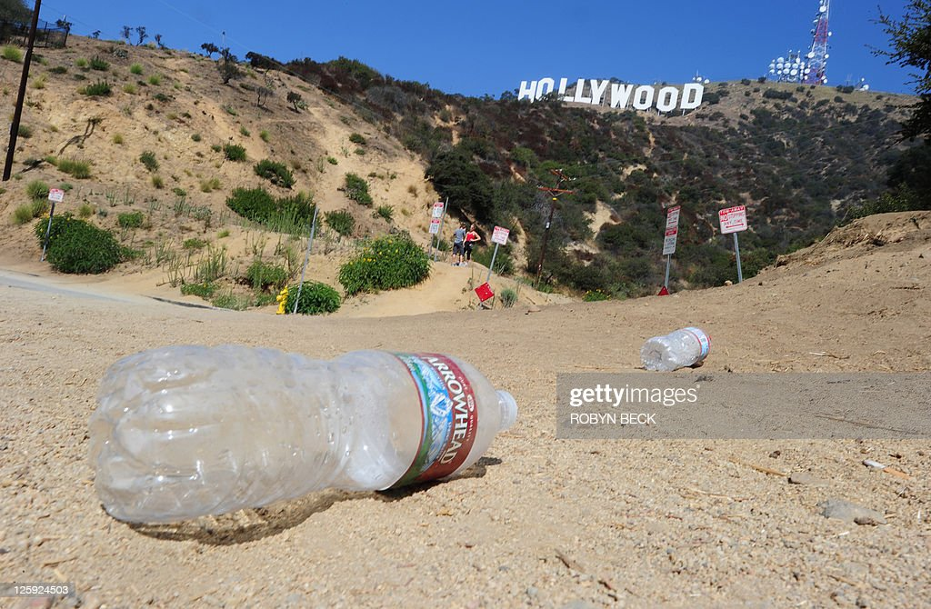 US-environment-technology-tourism Empty water bottles litter the ground at a popular Hollywood sign viewing area in the residential Hollywood Hills section of Hollywood, California, September 21, 2011. Travelers have long flocked to have their pictures taken with the vast sign behind them -- but with the advent of satellite navigation and Google Earth, they have begun to invade the Hollywood Hills neighborhood like never before. AFP PHOTO / ROBYN BECK