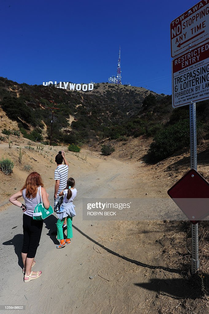 US-environment-technology-tourism Polish tourists Pawel Stepien, 18 (top), his sister Katie Stepien, 11, (R) and mother Maria Stepien stop for a snapshot in front of the Hollywood sign in a residential Hollywood Hills section of Hollywood, California, September 21, 2011. Travelers have long flocked to have their pictures taken with the vast sign behind them -- but with the advent of satellite navigation and Google Earth, they have begun to invade the Hollywood Hills neighborhood like never before.