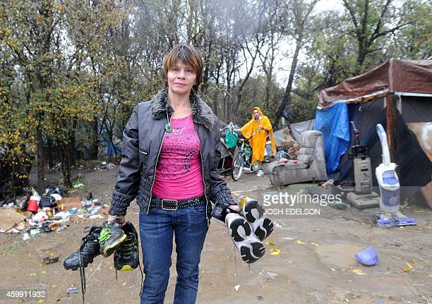 USPovertyHomelessTechnology Lilly Mei pauses for a photo after sifting through a pile of shoes at the Silicon Valley homeless encampment known as...