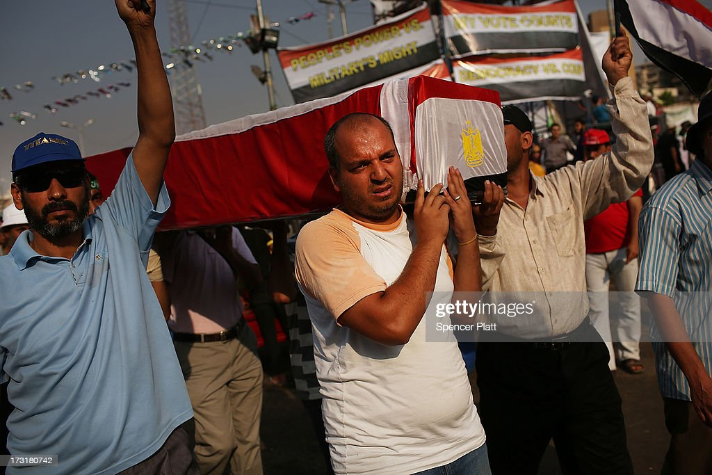 With an empty coffin representing some of those killed yesterday, pro-Mohamed Morsi supporters rally near where over 50 were purported to have been killed yesterday by members of the Egyptian military and police in early morning clashes on July 9, 2013 in Cairo, Egypt. The military, which took over control of the country from Muslim Brotherhood leader Morsi last week, has denied that they opened fire on the protesters and claim the shootings resulted after they came under attack from members of the Muslim Brotherhood. Egypt continues to be in a state of political paralysis following the ousting of Morsi by the military. Adly Mansour, chief justice of the Supreme Constitutional Court, was sworn in as the interim head of state in a ceremony in Cairo on the morning of July 4.