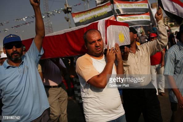 With an empty coffin representing some of those killed yesterday proMohamed Morsi supporters rally near where over 50 were purported to have been...