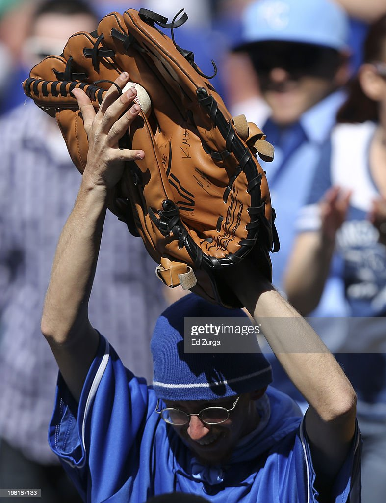 With an oversized glove, a fan catches a foul ball hit by Adam Dunn of the Chicago White Sox during a game against the Kansas City Royals in the seventh inning at Kauffman Stadium on May 6, 2013 in Kansas City, Missouri.