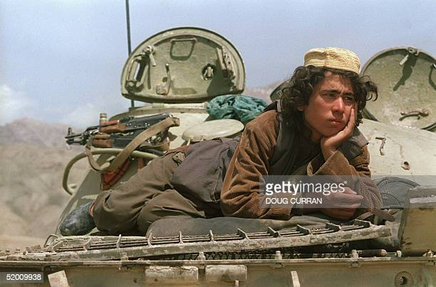 With arms at ease for the moment a militiaman loyal to Afghan army loyal to the JamiateIslami faction relaxes atop armoured personnel carrier 23...