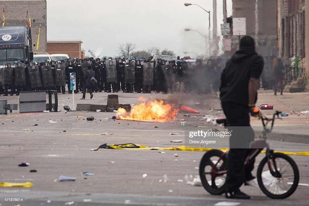 With Baltimore Police officers in riot gear lining the street a man stands at the corner of Pennsylvania Avenue and North Avenue April 27 2015 in...