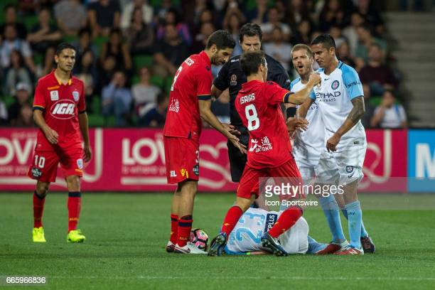 With Bruno Fornaroli of Melbourne City on the ground Isaias of Adelaide United Tim Cahill of Melbourne City and Luke Brattan of Melbourne City have...