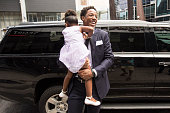 TORONTO ON JULY 14 With camera shy daughter Diar in his arms Toronto Raptors DeMar DeRozan and family arrived at the Real Sports Bar for a press...