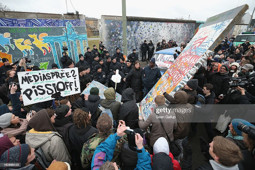 With chants of 'Fill the gap!' protesters attempt to bring forward a styorfoam replica of a piece of the Berlin Wall in order to fill a gap created by construction workers in the East Side Gallery, which is the longest still-standing portion of the former Berlin Wall, as police try to block the protestersl on March 01, 2013 in Berlin, Germany. A real estate developer is planning to build a 14-storey apartment building between the Wall and the Spree River, and needs to remove a 25-meter long Wall section in order to allow access to the construction site. Critics, including East Side Gallery mural artists and Spree River embankment development opponents, decry the move, citing the importance of the East Side Gallery's status as a protected landmark and a major tourist attraction. The East Side Gallery is approximately 1.3 kilometers long.