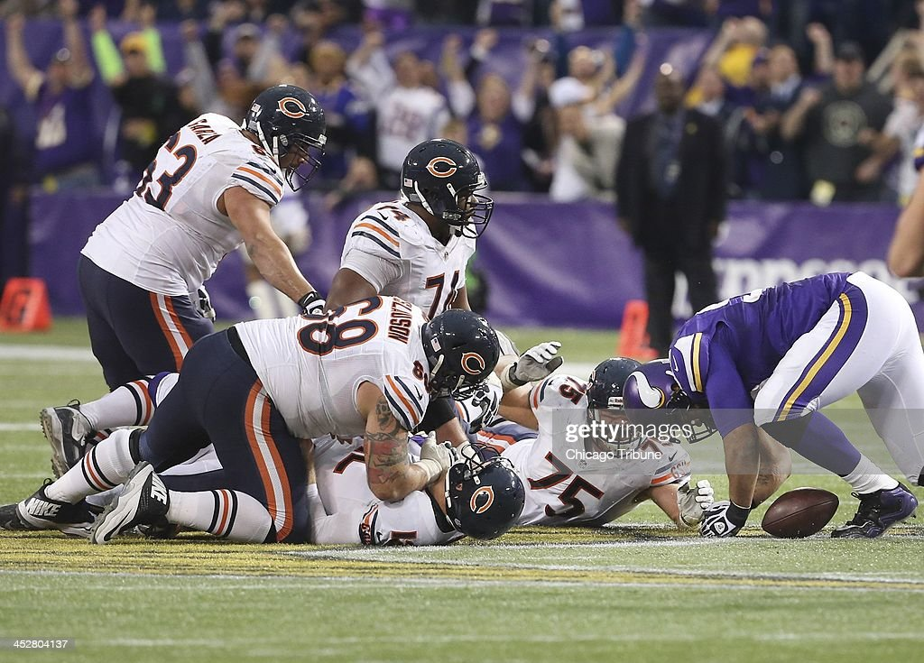 With Chicago Bears quarterback Josh McCown (12) on the ground, right, Minnesota Vikings defensive tackle Kevin Williams (93) reaches for a loose ball during overtime at the Hubert H. Humphrey Metrodome in Minneapolis, Minn., on Sunday, Dec. 1, 2013. The Vikings won, 23-20.