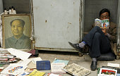 With 'Chinapoliticshistoryrevolutionlegacy'schedFEATURE A man reads a book sitting next to a portrait of the late Chinese leader Mao Zedong at a...