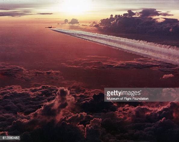 With contrails flowing behind a Boeing B52 Stratofortress strategic bomber flies off towards a sunny horizon