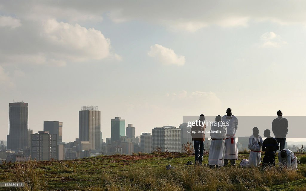 With downtown Johannesburg rising in the background, members of the Twelve Apostles Church of Christ pray on a hill in the Yeoville neighborhood April 4, 2013 in Johannesburg, South Africa. Members of the church, many of them immigrants from Zimbabwe, gather to pray in the open on the hill overlooking downtown Johannesburg because they say the Bible tells the faithful to go to the mountaintop to pray. According to government officials, Noble Peace Prize laureate and former South African President Nelson Mandela, 94, contiunes to recover from pneumonia after spending more than a week in the hospital, his third time since December.