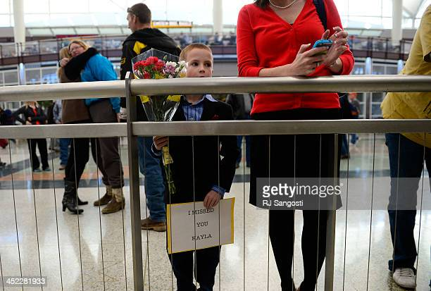 With flowers in hand eightyearold Benjamin Spiker waits with his mother at Denver International Airport for his friend to arrive 11 yearold Kayla who...