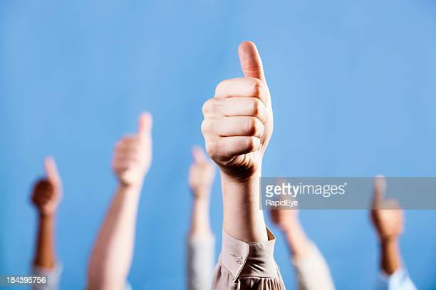With focus on foreground, mixed group gives thumbs up sign