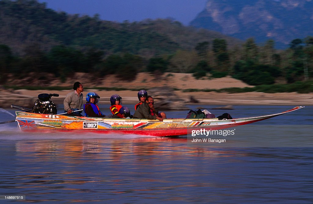 With helmets firmly fastened you can race down the Mekong River on the 007 'fastboat' outside Luang Prabang. : Stock Photo