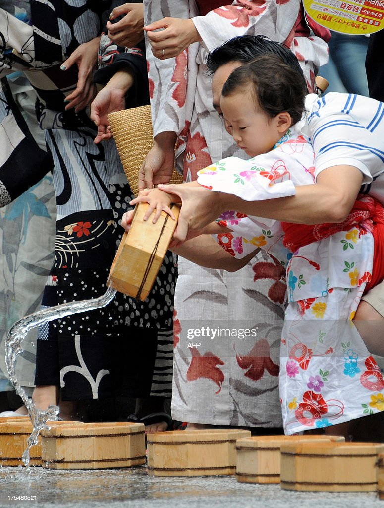 With help from her father a girl in a 'yukata,' or summer kimono, throws water to the ground at the Ginza shopping district in Tokyo on August 4, 2013. Hundreds of Yukata-clad people participated in the annual summer event to cool off amid high summer temperatures.