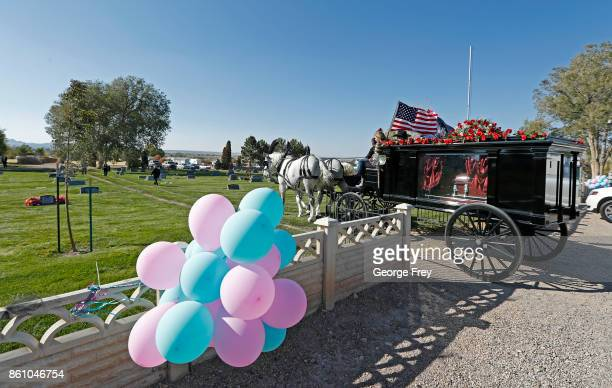 With her children on top a horse drawn hurst carries the casket of Heather Lorraine Alvarado through her neighborhood and in the cemetery where she...