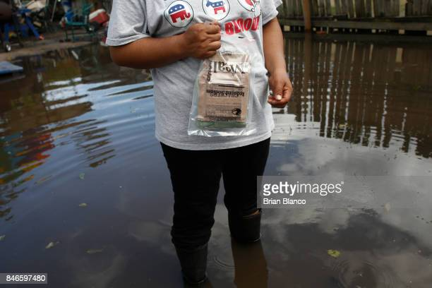 With her home surrounded by water that she and neighbors fear may be contaminated by waste water a resident holds an emergency food ration as she...