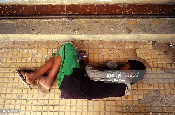 With his bag of glue wrapped tightly in his hand a teenage street kid lies passed out on a sidewalk with a glue high He is part of about 20 kids and...