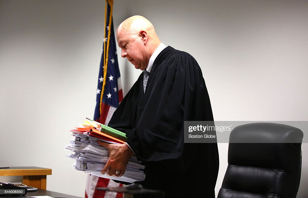 With his hefty stack of documents and notes, Judge George Phelan leaves the bench at the end of the day. Attorneys representing various factions of Sumner Redstone's family argue over who should gain control of his media companies, in Norfolk County Probate Court in Canton, Mass., on June 30, 2016.