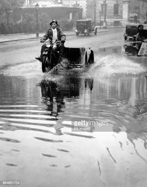 With his motorbike and sidecar an adventurous motorcyclist ploughs his way through the swamped roadway on Birdcage Walk London where the huge deluge...