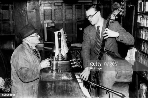 With his score propped against the beer pumps Victor Cook landlord of the ParkLane Tavern Cradley near Wolverhampton practices on his bull fiddle...