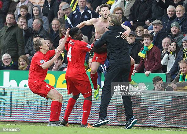 With his shirt off Liverpool's English midfielder Adam Lallana celebrates scoring their late winning goal Liverpool's German manager Jurgen Klopp...